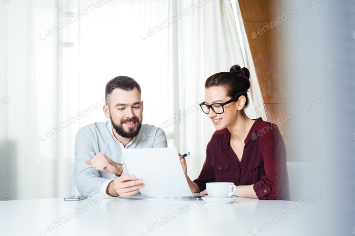 Two happy businesspeople discussing new project in meeting room