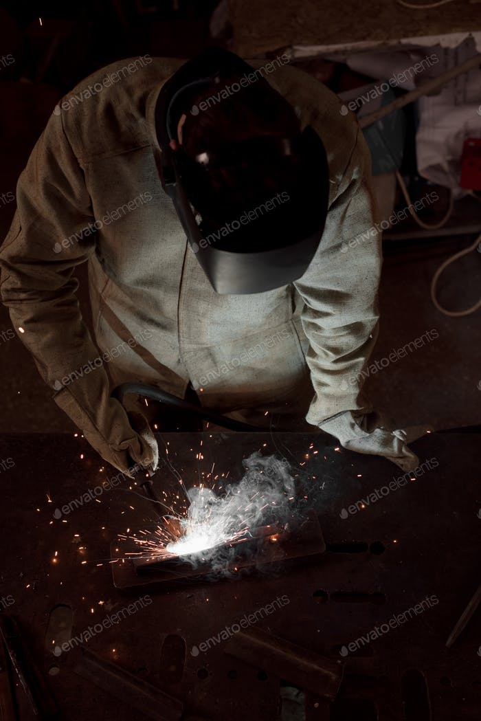 High Angle View of Manufacture Worker Welding Metal With Sparks at Factory