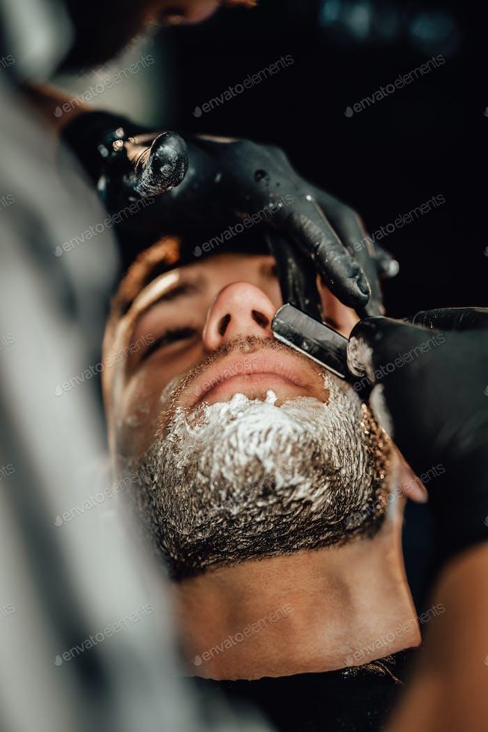 Brutal guy is shaving by professional hairdresser