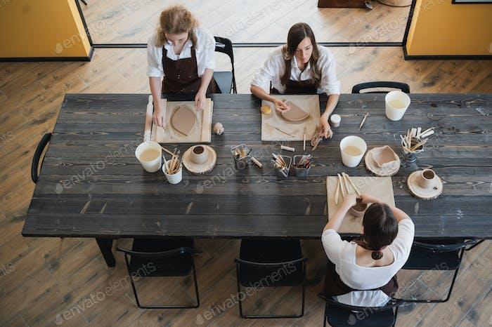 Vista superior de las artistas femeninas esculpiendo diferentes productos de arcilla en una gran mesa de madera con cerámica
