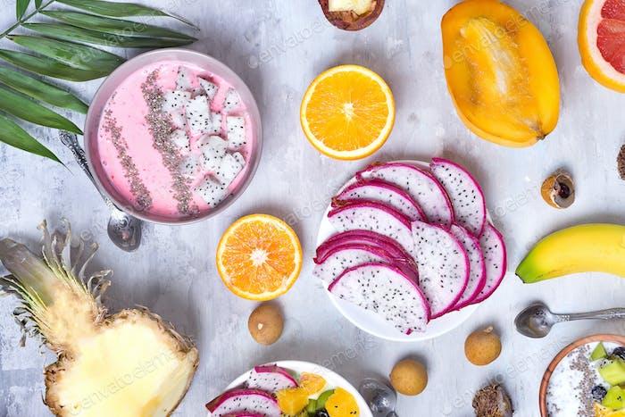Frühstückstisch mit Joghurt Erdbeer-Smoothie Schalen und frischen tropischen Früchten auf einem grauen Stein