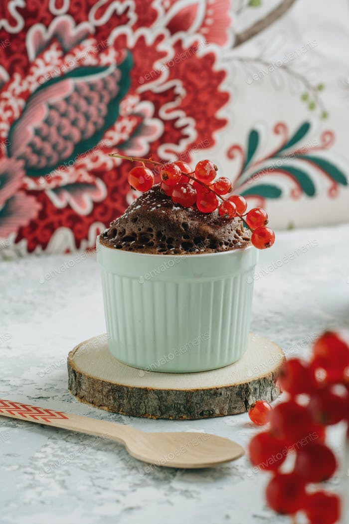 Chocolate cake in the cup with currants and sugar glass.