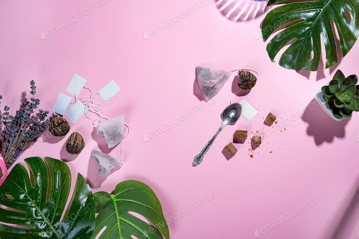 Workspace frame with green tropical leaf and tea cup, tea bag and sugar on pastel pink background