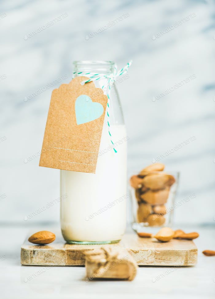 Fresh vegan dairy-free almond milk in bottle with craft label
