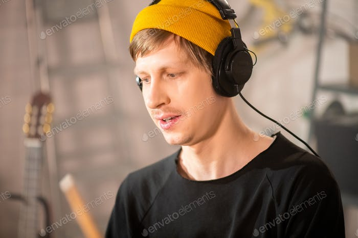 Young drummer in beanie and headphones recording new music in garage