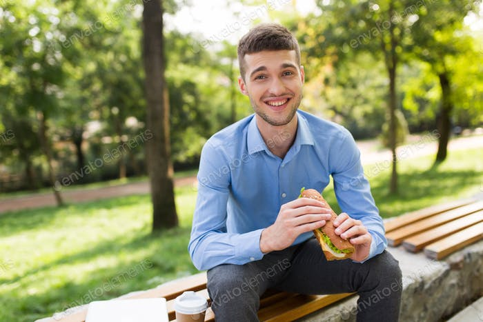 Young joyful man in blue shirt sitting on bench with sandwich in