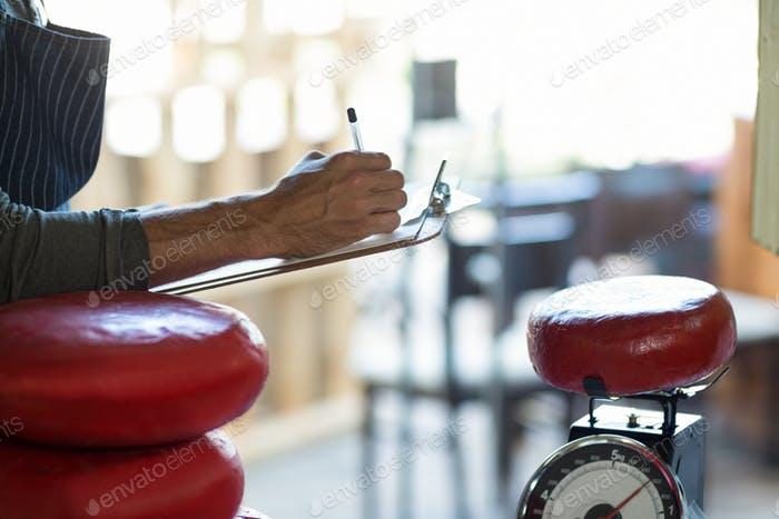 Mid section of salesman writing on clipboard at counter