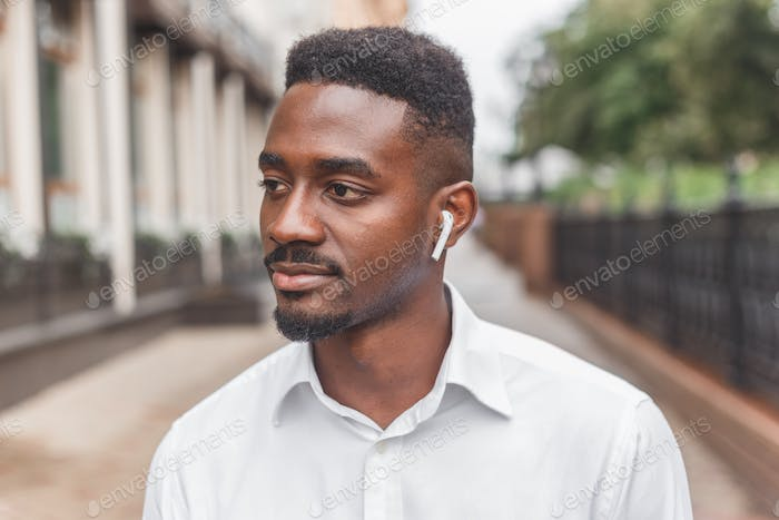 Young black businessman with wireless earphones walking outdoors