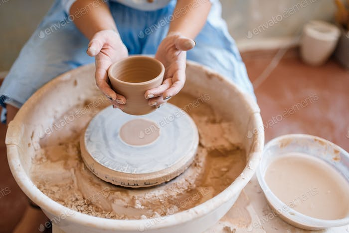 Female master holds wet pot over the pottery wheel