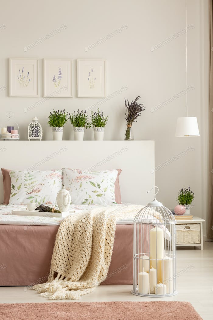 Candles in bird cage placed on the floor by double bed with brea