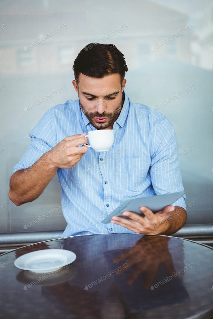 Businessman drinking coffee while watching tablet outside the cafe