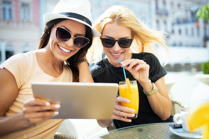 Holidays, tourism and internet - beautiful girls looking at tablet pc in cafe outside