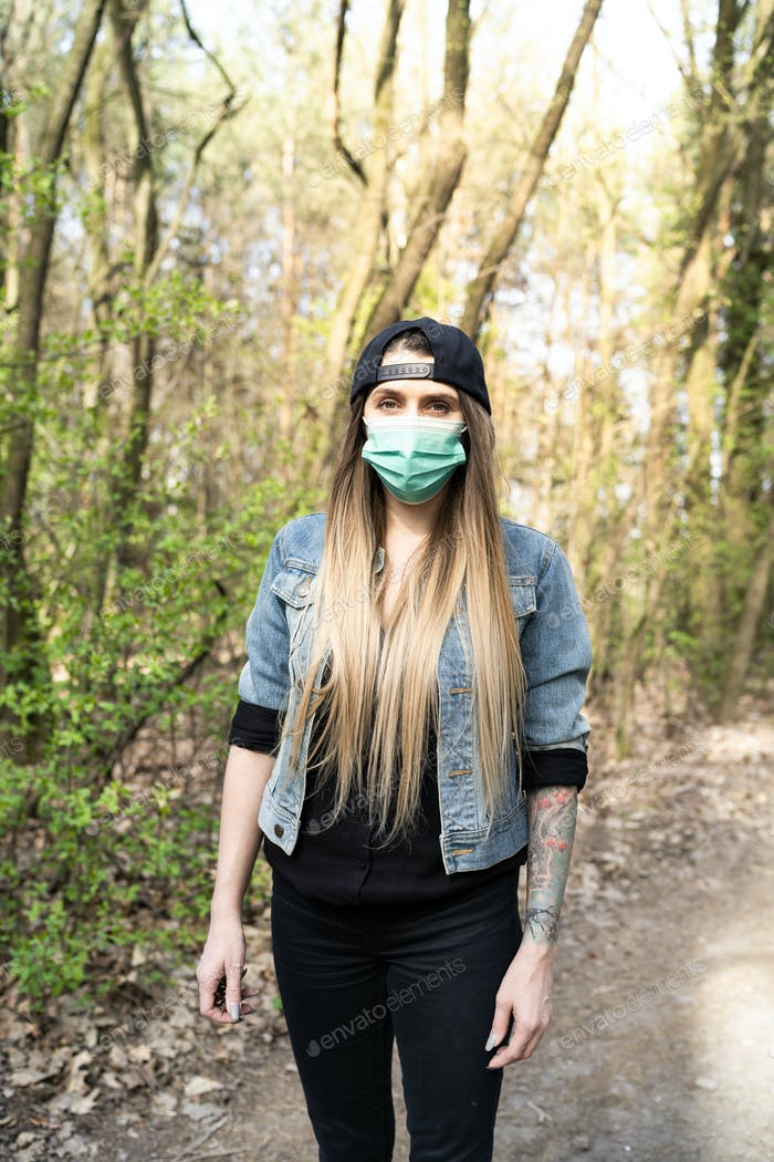 Young Casual Woman Wearing Face Mask Walking in Forest. Leisure Activity in Coronavirus Pandemia