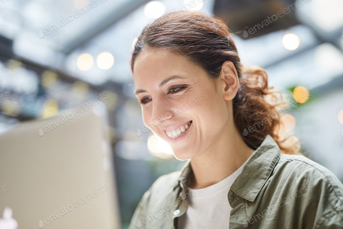 Happy Woman Using Laptop in Cafe
