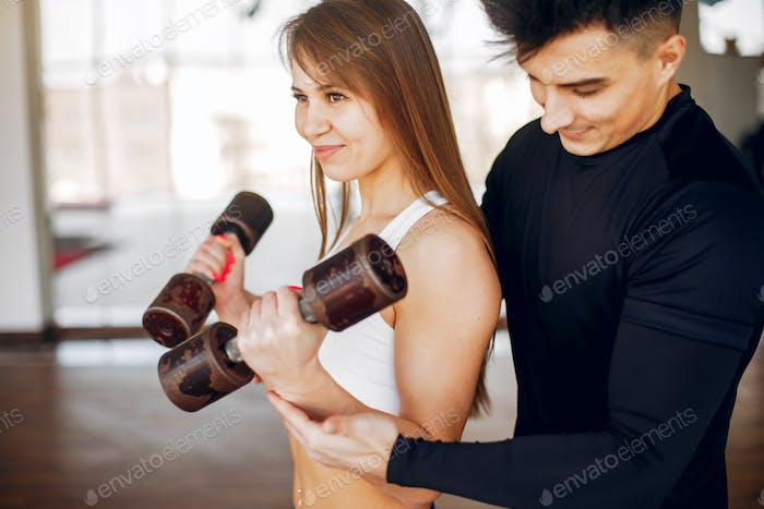 A beautiful sports couple is engaged in a gym