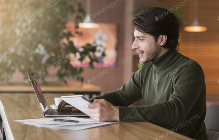 Journalist working on new article online at cafe