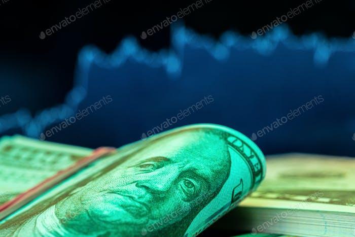 Dólares delante de un monitor con gráfico de precios. Forex y trading