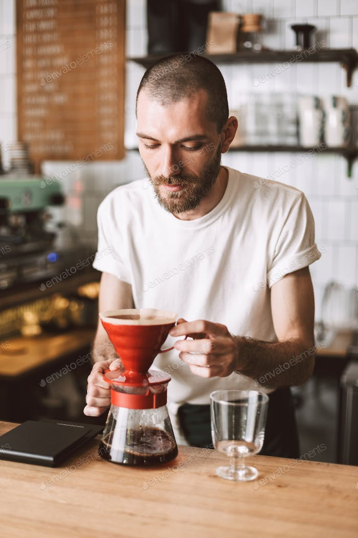 Young pensive barista standing at bar counter and preparing pour over coffee while working in cafe