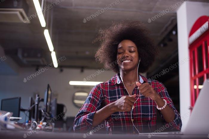 black woman in modern office speeking on phone over earphones
