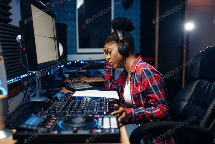 Female sound operator in audio recording studio
