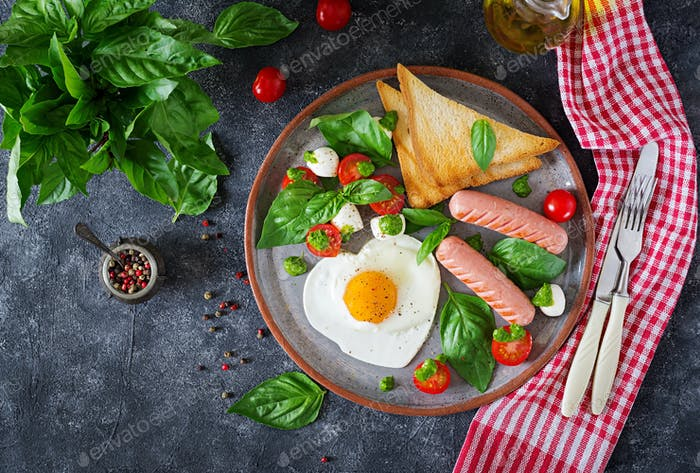 fried eggs in the shape heart, sausage, toast and caprese salad of a tomato, basil and mozzarella