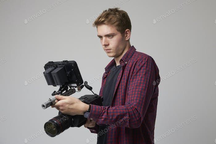 Studio Portrait Of Male Videographer With Film Camera