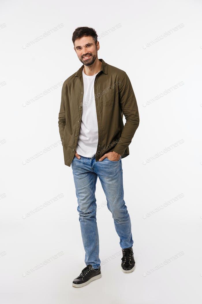 Durchgehende vertikale Schuss gut aussehende Macho stilvolle moderne Kerl, unrasiert, tragen Jeans und Mantel