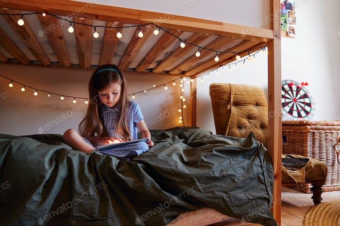 Chica joven sentada en la cama en casa decorada con luces de hadas usando tableta digital