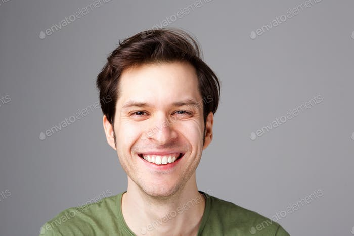 Close up happy young man standing by gray wall