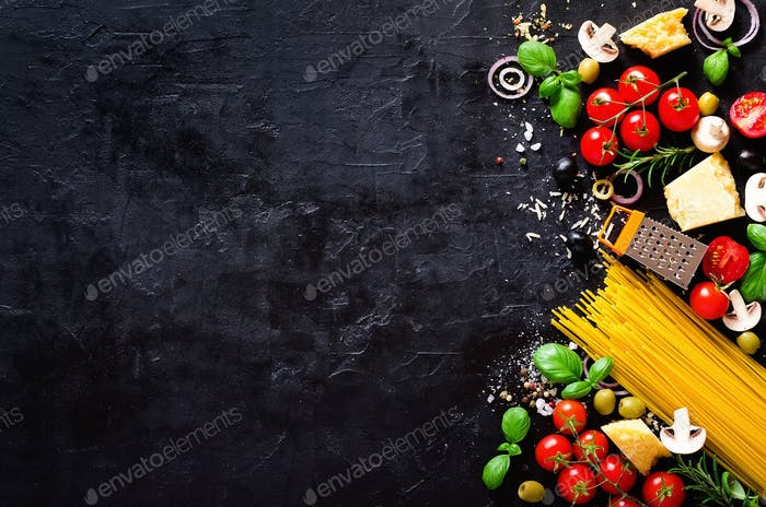 Food ingredients for italian pasta, spaghetti on black stone slate background. Copy space of your
