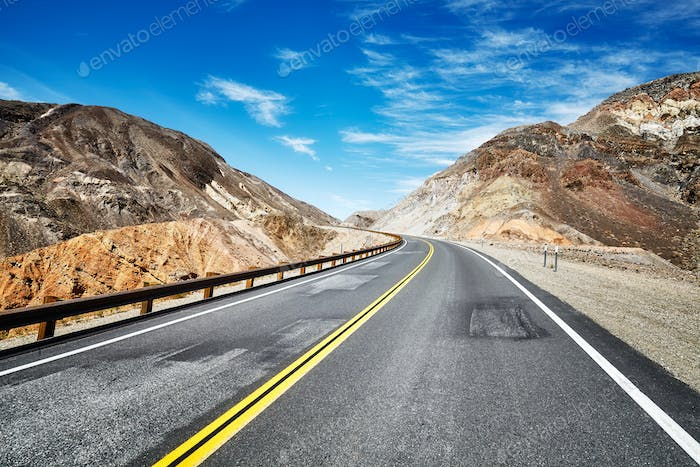 Empty highway in deserted mountainous terrain, USA.