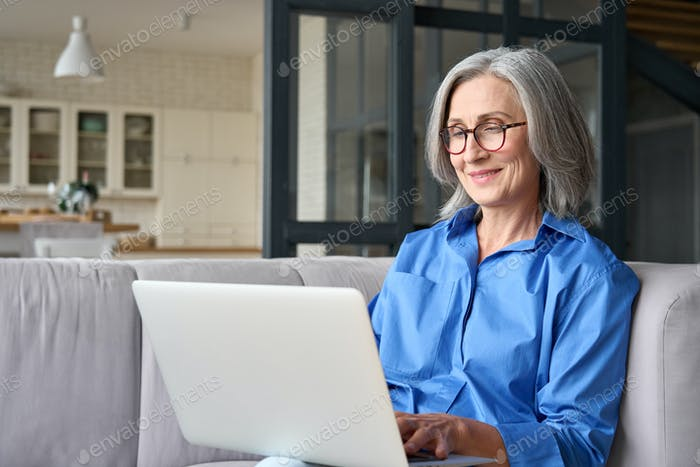 Older 60 woman using computer technologies at home sitting on sofa.