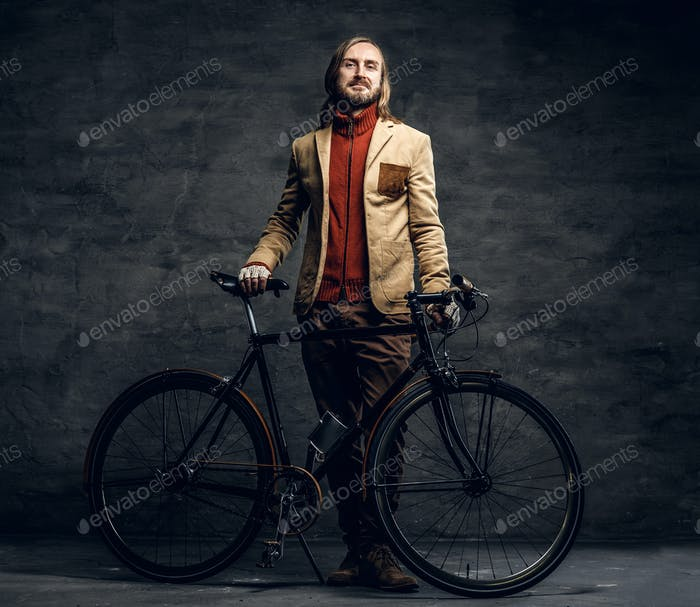A man posing with single speed bicycle over grey background.