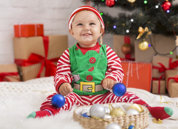 Joyful baby playing with Christmas decorations under xmas tree