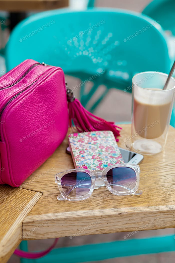 objects arranged on table in city cafe in street, woman accessories
