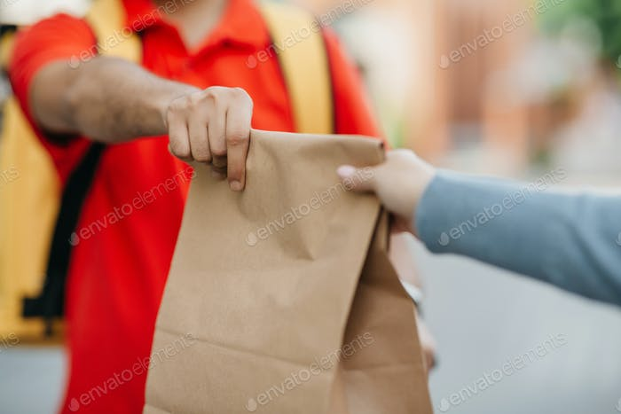 Give order to client in town. Deliveryman in uniform with yellow backpack holds paper bag