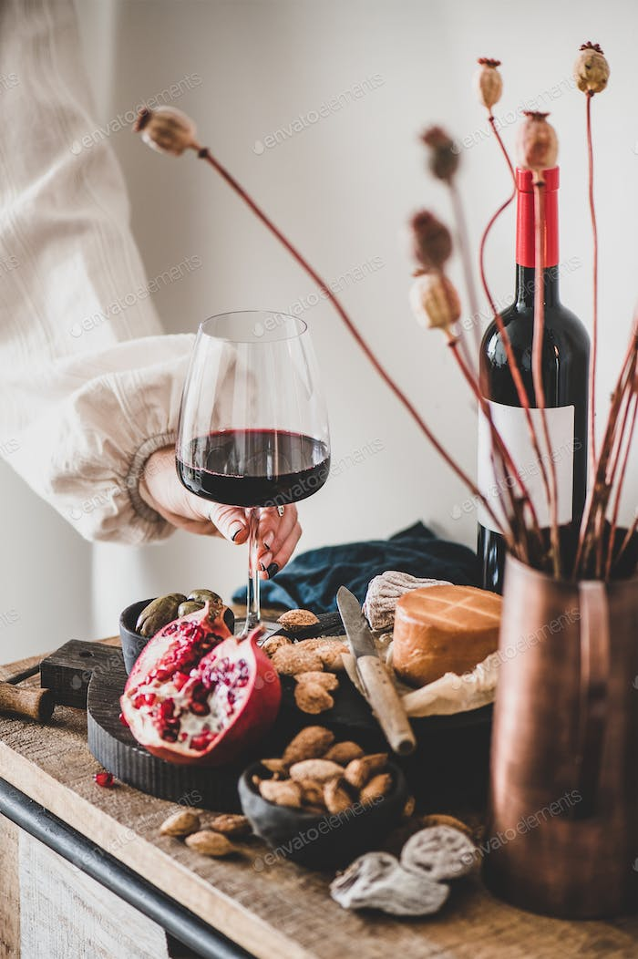 Womans hand holding glass of red wine over various snacks