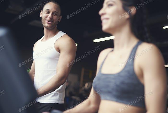 Pareja de adultos jóvenes haciendo ejercicio en cinta de correr