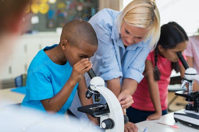 Children scholar looking through microscope