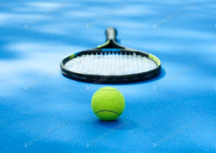 Tennisball liegt in der Nähe von Schläger auf blauem Cort Teppich