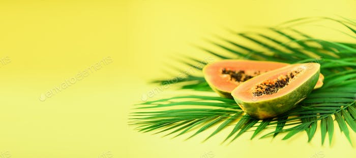 Papaya fruit over tropical green palm leaves on yellow background. Copy space. Pop art design
