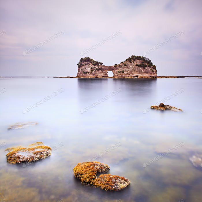 Hole island and rocks in a tropical blue ocean. Cloudy sky.