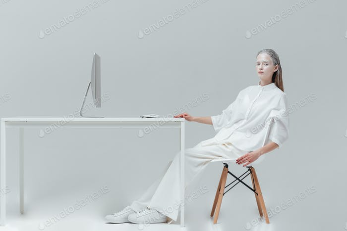 Woman relaxing at the table with computer on the chair