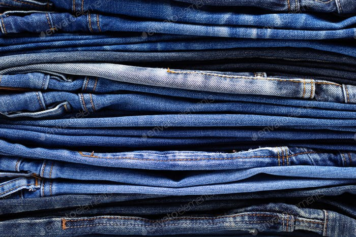 Stack or pile of denim jeans as background texture