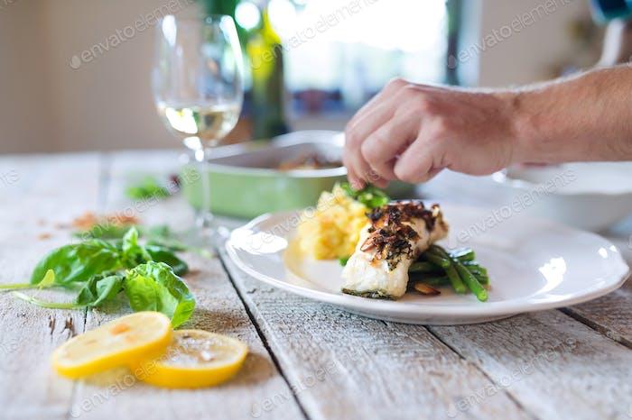 Unrecognizable man serving zander fish fillets on a plate
