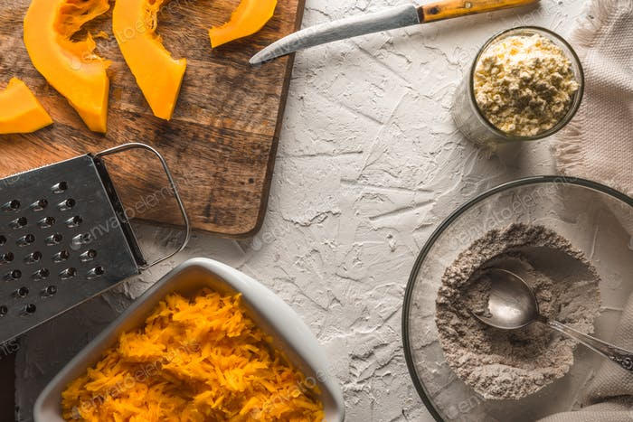 Grated pumpkin, flour on a white table for making pancakes
