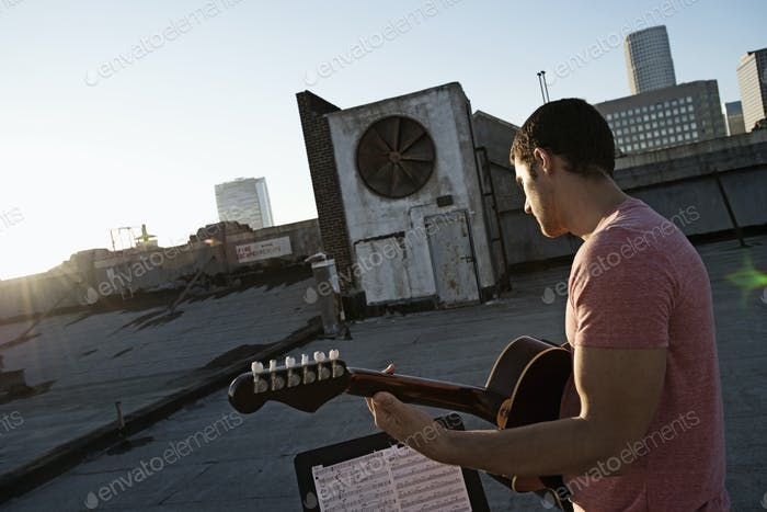 A man playing a guitar, sititng on a rooftop terrace overlooking the city at dusk.