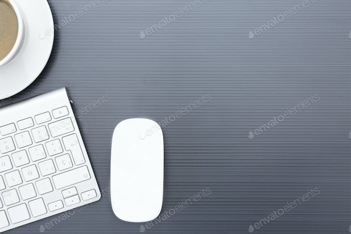 grey business desk with a wireless mouse