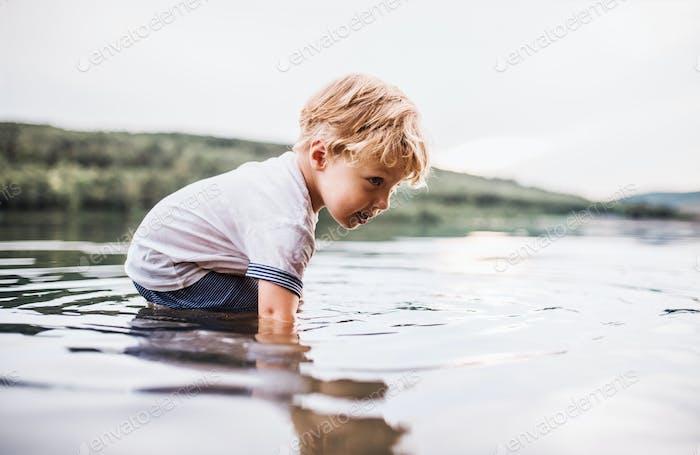 Un niño pequeño jugando al aire libre junto al río en verano.