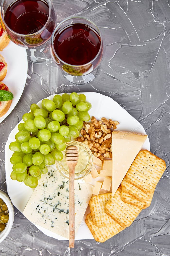 Cheese plate variety, and wine in glasses